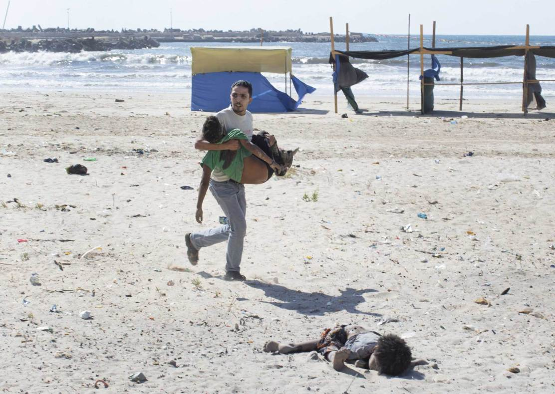 A man carries a child as another lies dead after two explosions on a beach in Gaza.
